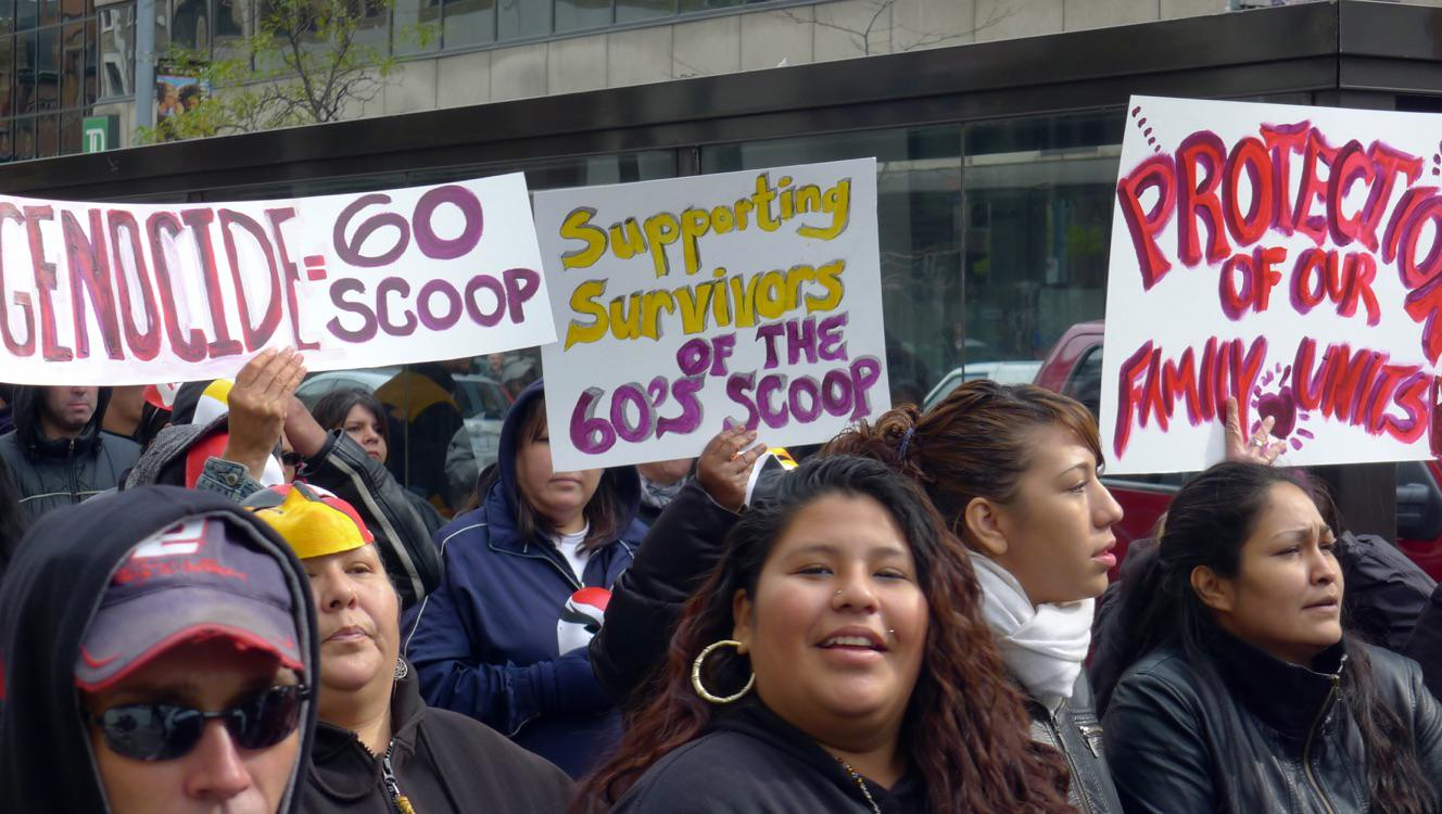 People holding signs marching in a Sixties Scoop protest.