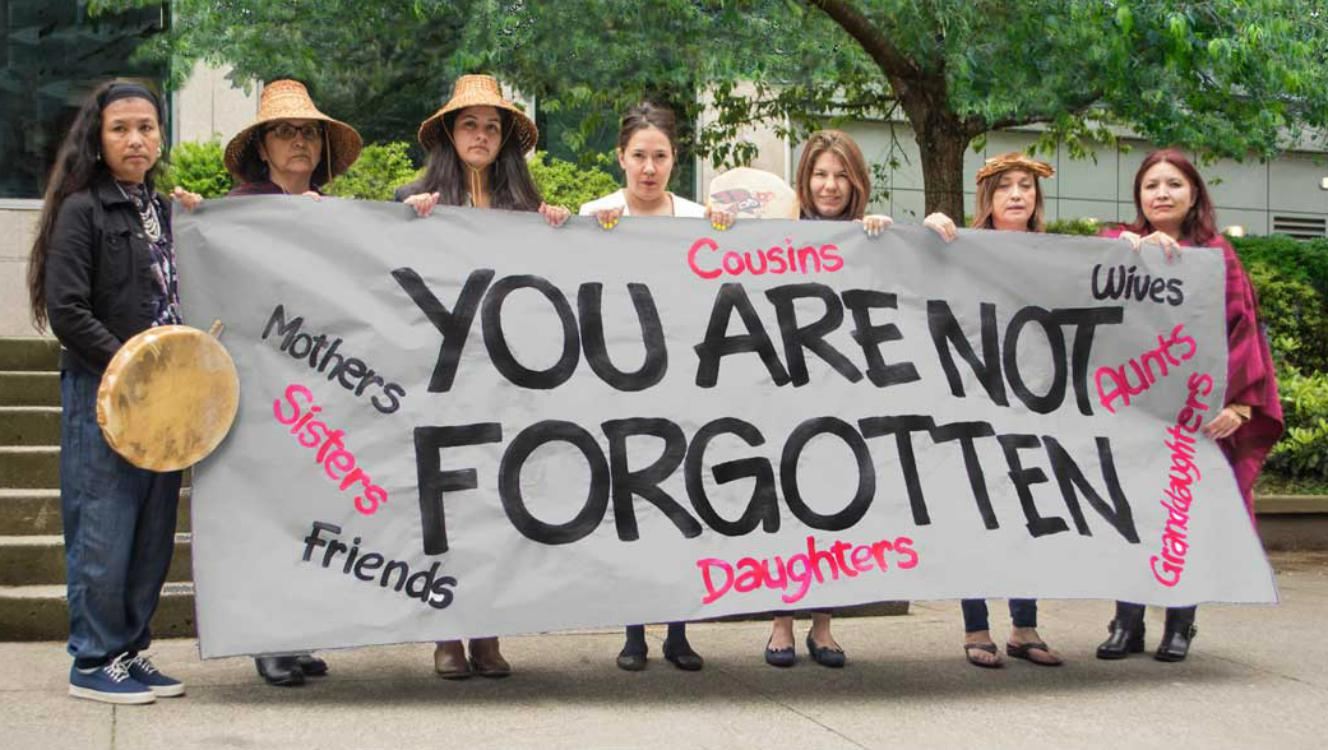 Seven women holding a hand-painted sign that says You are not forgotten.